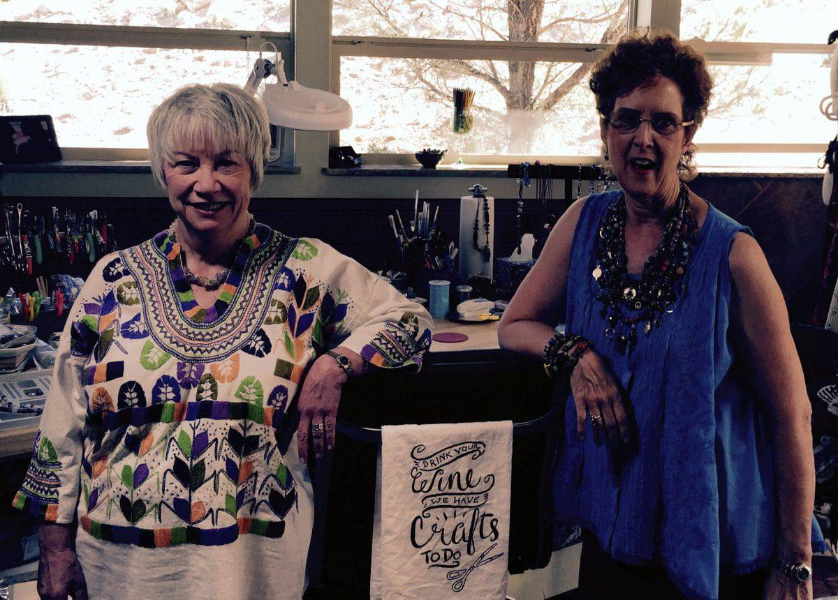 """Susan Wyngaard and Mary Ellen stand in front of a towel that says """"Drink your wine. We have crafts to do."""""""